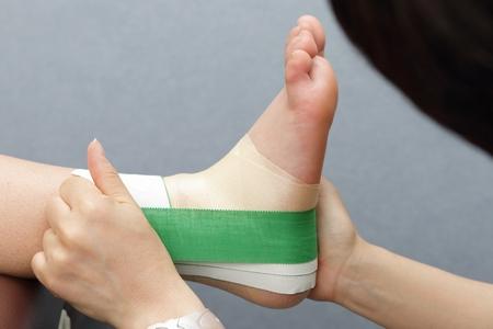 非伸縮テープを使用し、足の内側から外側に向かって強く引っ張りながらテープを3本巻く